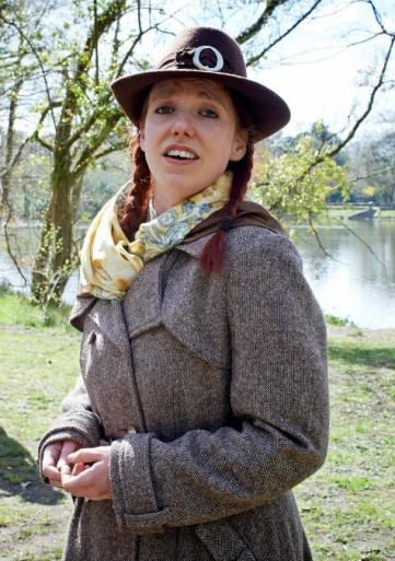 Gillian Dean as Helena in A Midsummer Night's Dream by William Shakespeare. Taking Flight Theatre Company 2013. Gillian is wearing a brown hat, tweed coat and yello scarf. Her red hair is in two plaits.