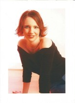Gillian Dean studio shot. Gillian has short red hair, is wearing a blackoff the shoulder jumper and leaning towards the camera, smiling.