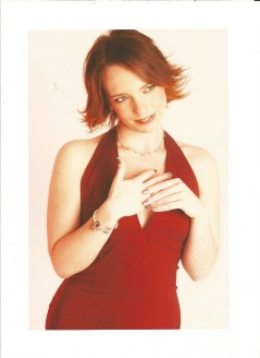 Gillian Dean studio shot. Gillian is wearing a low v-neck burgundy dress, playing with a ring on her finger and smiling whilst looking to the side.