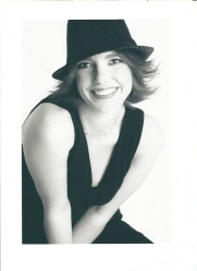 Gillian Dean studio shot. Gillian is wearing a black trilby hat, a black v-neck vest and is leaning forward smiling at the camera.
