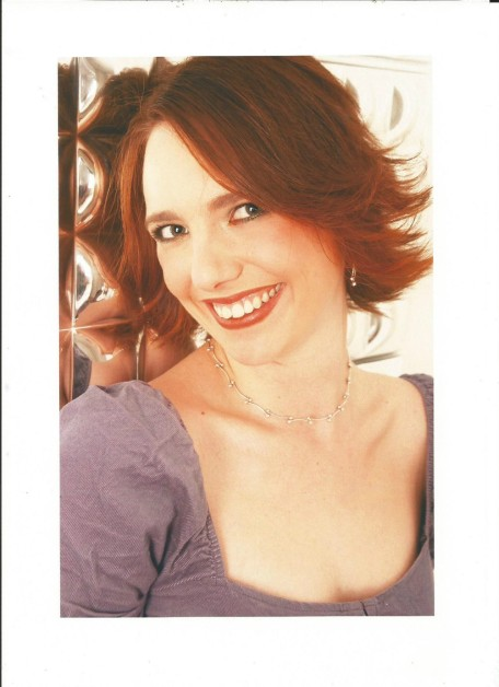 Gillian Dean studio shot. Gillian is smiling at the camera and wearing a lilac blouse.