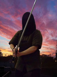 Gillian Dean in full fencing mask and padded jacket with German longsword against a sunset sky.