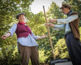 Gillian Dean as Victoria Stannard. Left, Gillian stands with arms wide smiling wearing a flat cap, loose shirt, red waistcoat, neckerchief and corduroy trousers. Right stands a man pointing at Gillian wearing blue trousers, a shirt, waistcoat, neckerchief and flat cap. Between them is the mast and name plate of the boat Perseverance.