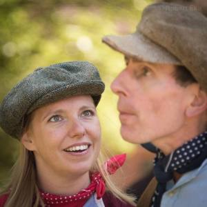 Close up. Left, Gillian Dean as Victoria Stannard wearing flat cap and red neckerchief smiles up a a man, right, wearing a flat cap and blue neckerchief.