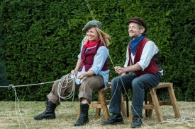 Left Gillian Dean as Victoria Stannard sits on a stool coiling a rope. Right a man sticks on a stoolholding a rope that is coming from above him. Both are smiling.