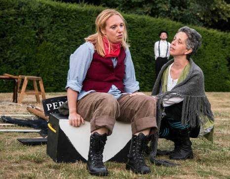Centre, Gillian Dean as Victoria Stannard sits on a box looking dejected. Right, a woman in a shawl kneels next to Gillian