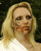 Colour shot of Gillian Dean as Agaue in Toxin. She is wearing gold lipstick, black eyeliner and eye shadow, her face is smeared with blood.