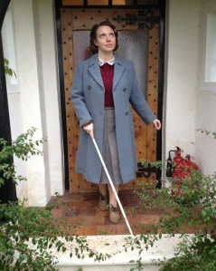 Colour picture of Gillian Dean in front of a cottage door. She is holding a white cane and wearing 1940s clothes