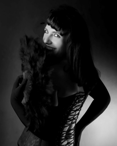 Black and white picture. Gillian Dean looking over her shoulder, smiling through a black feather fan. She is wearing a corset.