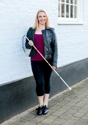 Gillian Dean on a street, holding a white guide cane and standing against a house wall. She is wearing a leather jacket, pink vest, cropped black trousers and heeled lace up shoes.