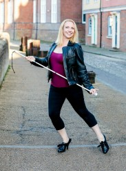 Gillian Dean on a street, holding a white guide cane and striking a Broadway dance pose. She is wearing a leather jacket, pink vest, cropped black trousers and heeled lace up shoes.