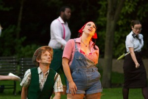 Gillian Dean as Jacquenetta on Love's Labours Lost stands centre frame in short dungarees, a red checked shirt and red bandana, singing. Left, a man kneels looking up at Gillian.