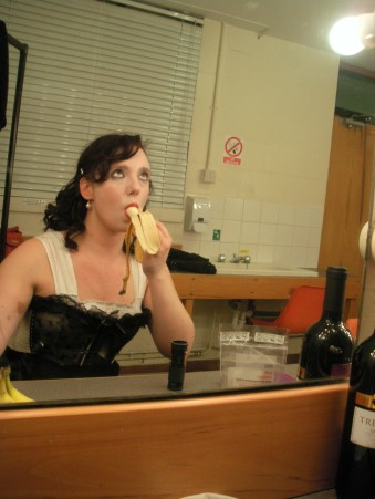 Gillian Dean as Mrs Farley in Playhouse Creatures. Gillian sits eating a banana and looking into a mirror, she is wearing a black and white corset.