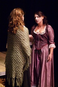 Gillian Dean as Mrs Farley in Playhouse Creatures. Gillian, wearing elaborate pink dress, stands talking to Nell gwynn