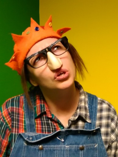 Gillian Dean as Wark/The Ugly Girl. She is looking totally baffled, wearing a Groucho Marx nose and glasses set, an orange feltjesters hat and mismatching checked shirt.